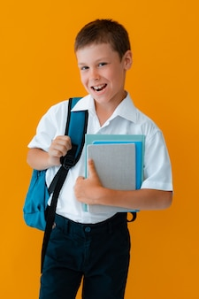 Smiling cheerful schoolboy against yellow background. a child with a backpack, books and notebooks. the boy is ready to study. back to school.