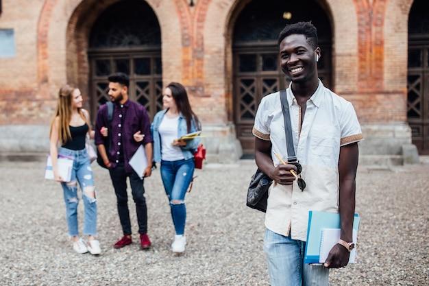 本を持って立っている陽気な成功したアフリカのオタク学生の笑顔