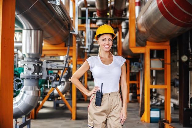 Улыбается веселая успешная независимая работница в рабочем костюме и с защитным шлемом на голове, стоя на теплоцентрали и глядя в камеру. женщина делает мужскую работу концепции.