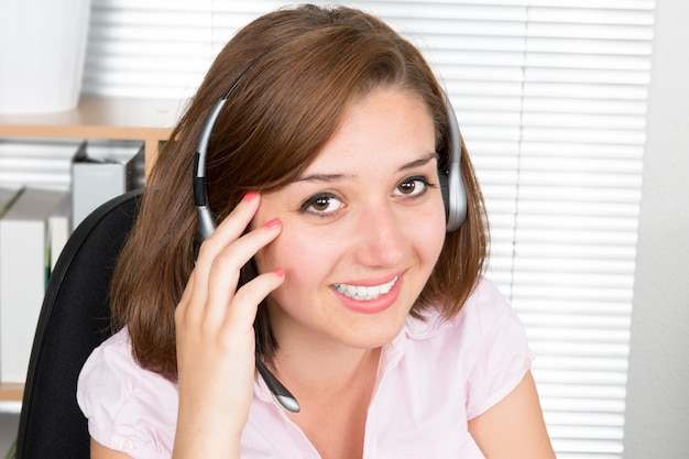 Smiling cheerful support phone operator in headset at office