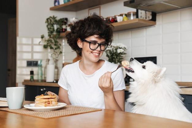 自宅のキッチンに座って、パンケーキを食べながらおいしい朝食を食べて陽気な女性の笑顔