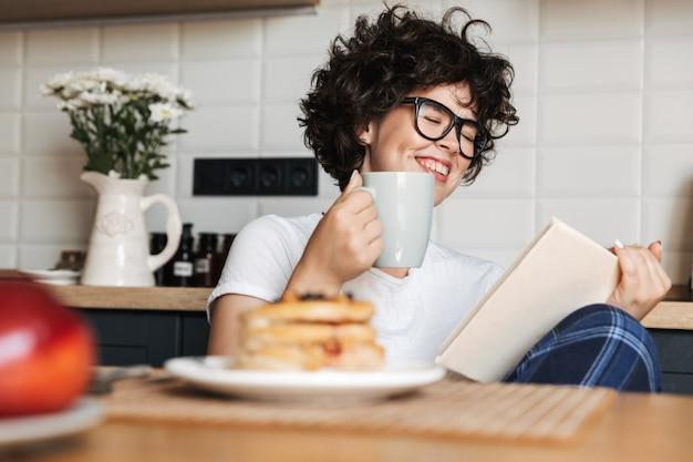 自宅のキッチンに座って、本を読んでおいしい朝食を食べている陽気な女性の笑顔