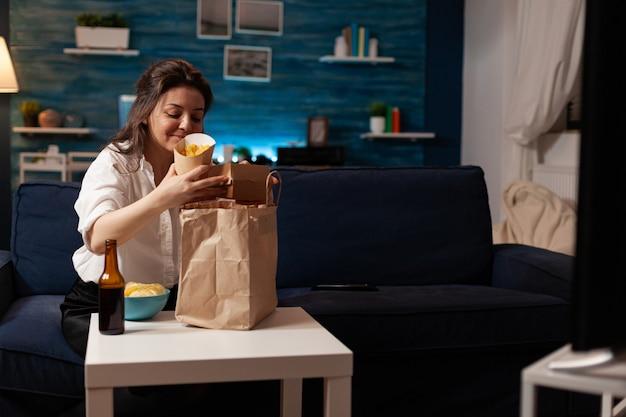 Sorridente donna allegra che disimballa la consegna del pasto fast food seduta sul divano durante il cibo spazzatura consegnato a casa