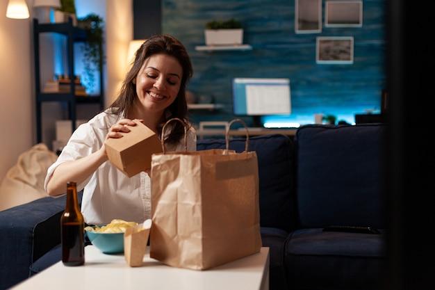 웃고 있는 쾌활한 여성이 소파에 앉아 집으로 배달되는 시식 패스트푸드 포장을 풀고 있다