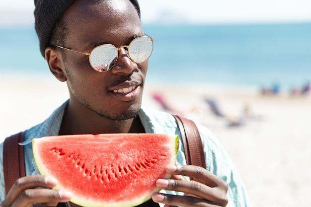 Улыбающийся веселый молодой черный хипстер, держащий большой кусок спелого и сочного арбуза с ожидающим взглядом