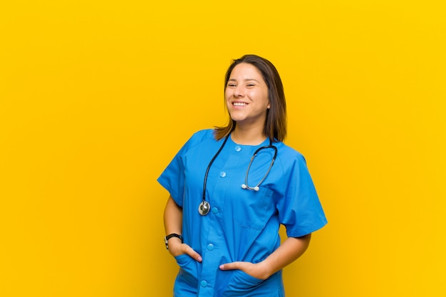 Smiling cheerfully and casually with a positive, happy, confident and relaxed expression isolated on yellow wall