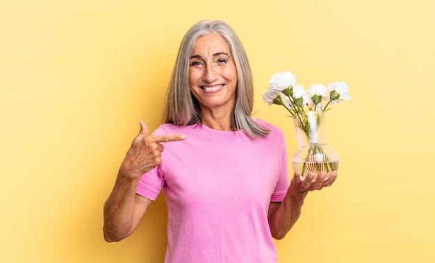 元気に笑って、幸せを感じて、横と上を指して、装飾的な花を持っているコピースペースにオブジェクトを示しています