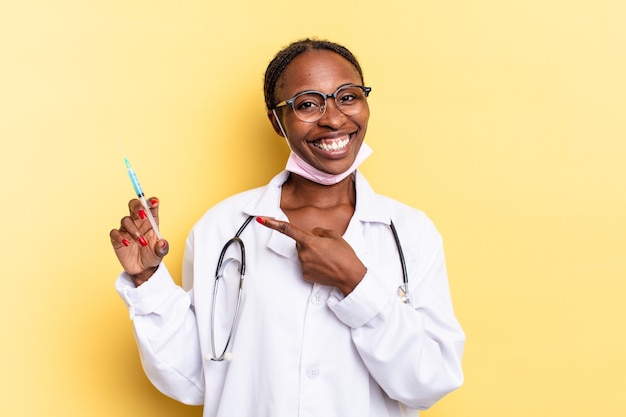Smiling cheerfully, feeling happy and pointing to the side and upwards, showing object in copy space. physician and syringe concept
