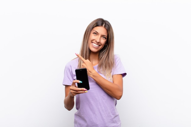 Smiling cheerfully, feeling happy and pointing to the side and upwards, showing object in copy space