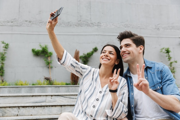 Smiling cheery young couple outdoors take a selfie by mobile phone.