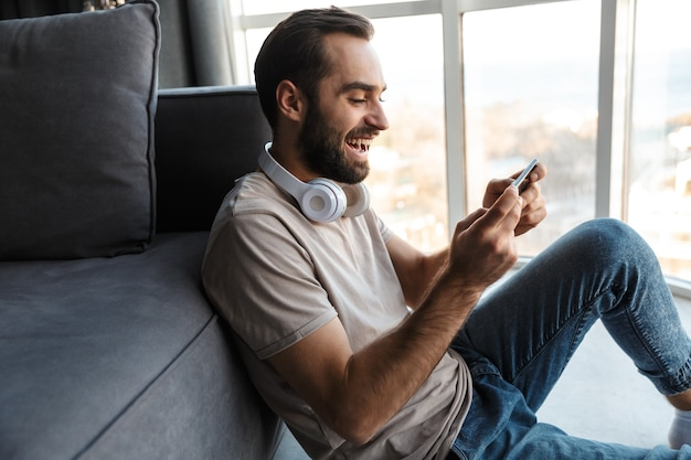 A smiling cheery young man indoors at home play games by mobile phone sit on floor.