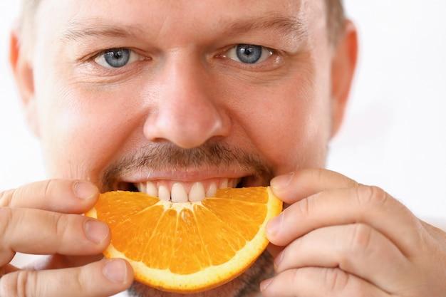 Smiling chef eating tropical citrus slice portrait