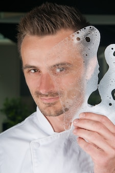 Smiling chef holding decorative ice plate in front of his face