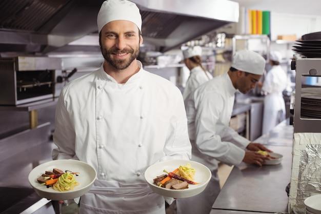 キッチンでおいしい料理を保持している笑顔のシェフ