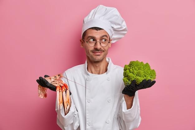 웃는 요리사는 옆으로 기뻐하고 요리사 모자와 유니폼을 입고 녹색 브로콜리, 크레이 피시를 들고 카페에서 채식주의자를위한 최고의 메뉴를 제안합니다.