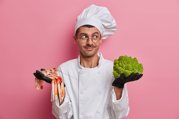 Smiling chef looks gladfully aside, wears cook hat and uniform, holds green broccoli, crefish, suggests best menu for vegetarians in cafe