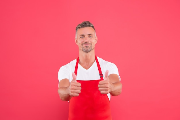 Smiling chef man show thumb up. professional chef wanted. male chef cook in red apron. businessman wear apron in coffee shop. his favorite work. portrait of handsome professional chef. best from best.