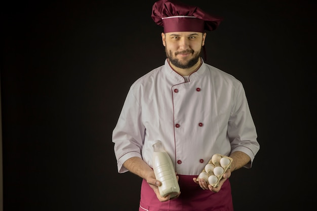 Smiling chef man in uniform holds bottle of milk and eggs black