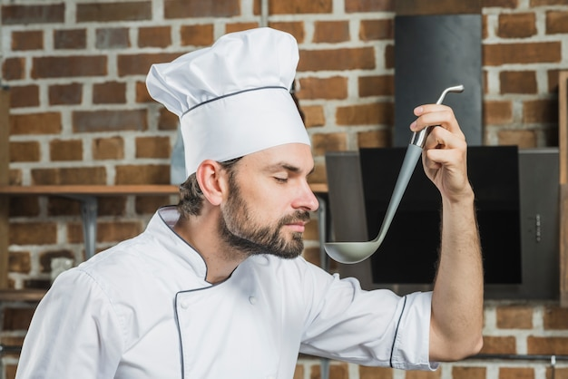 Smiling chef with eyes closed smelling the soup in kitchen