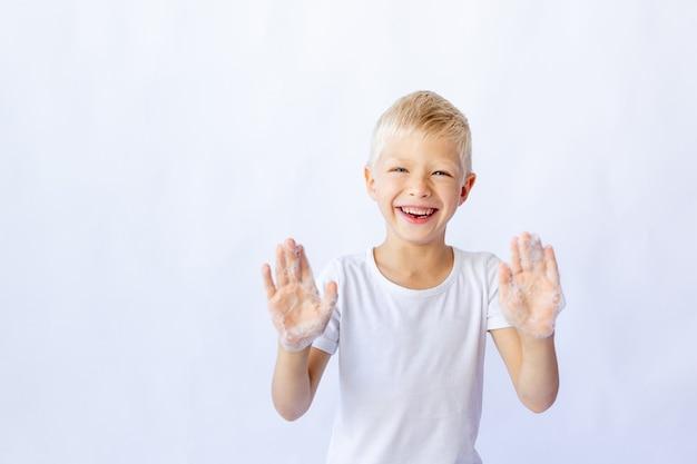 白いtシャツを着た子供の少年の笑顔は泡で彼の手を示しています