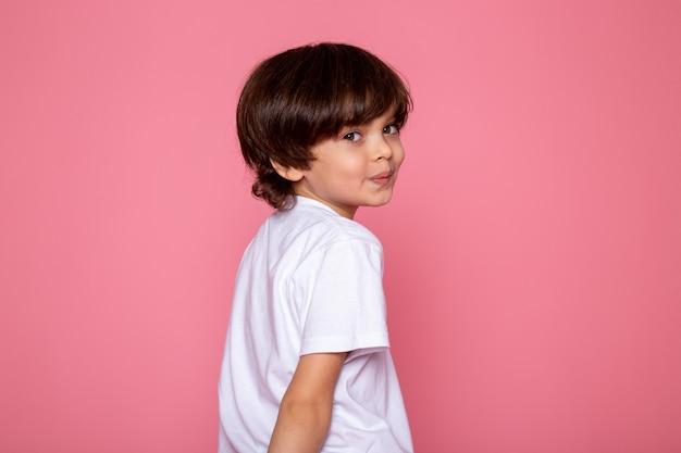 Ragazzo adorabile sorridente piccolo adorabile sveglio in maglietta bianca sullo scrittorio rosa