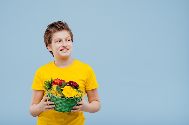 Улыбающийся мальчик с корзиной цветов в руке, в желтой футболке, изолированной на синей стене, копией пространства, видом в профиль