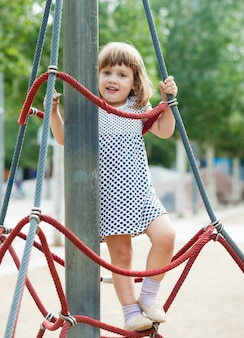 Smiling child climbing at ropes on playground