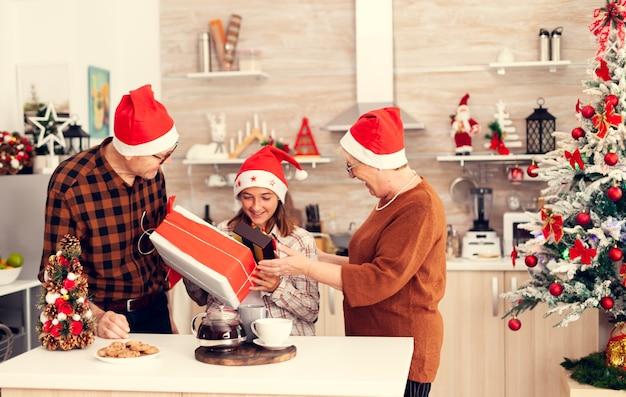 Улыбающийся ребенок во время празднования рождества получает подарочную коробку от веселого старшего мужчины и женщины