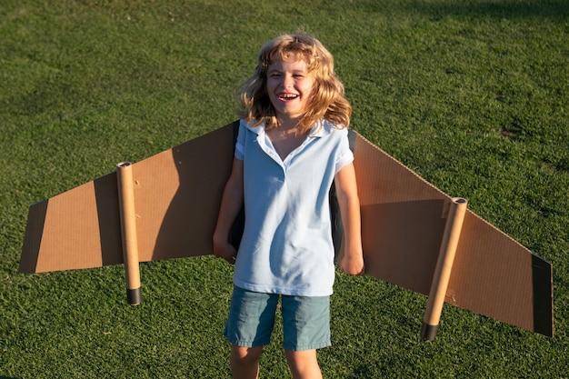 飛行機で飛んでいる笑顔の子供は段ボールの翼の工芸品を作りました。夢、想像力、幸せな子供時代。旅行と夏休みのコンセプト。