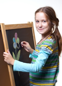 Smiling child girl drawing with chalk on a wooden easel