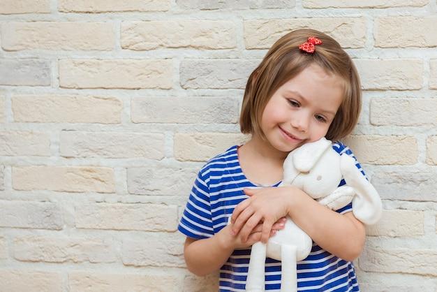 Улыбающаяся девочка, держащая в руках любимую игрушку, чучело кролика