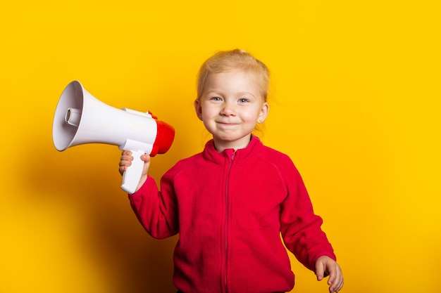 Smiling child girl holding a megaphone on a bright yellow background.
