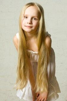 Улыбающаяся девочка с длинными светлыми волосами - портрет