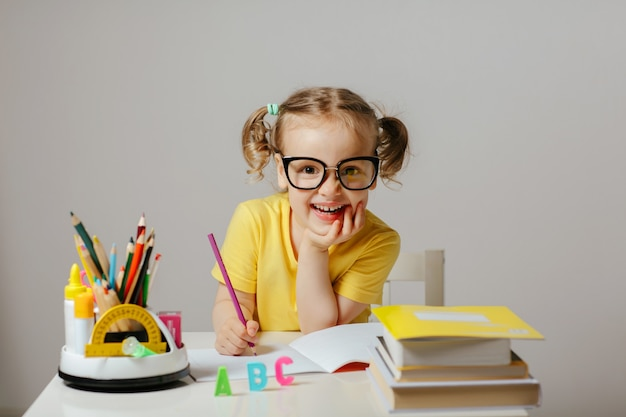 A smiling child in glasses sitting in the classroom with school supplies