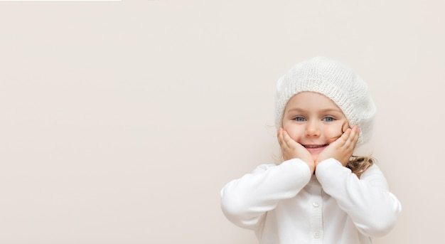 Smiling child in handmade woolen knitted headband and white sweater isolated on beige background