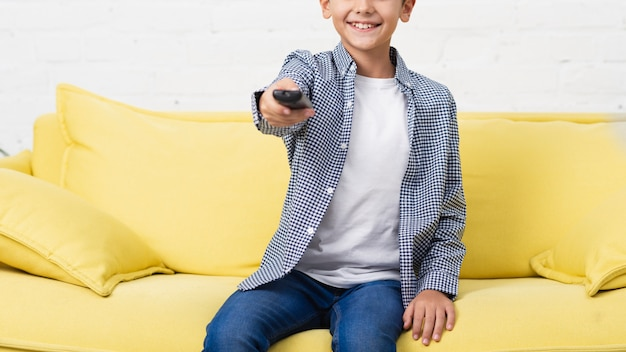 Smiling child holding a remote control