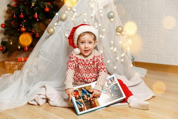 Улыбающийся ребенок, глядя на фотоальбом дома, семейные уютные моменты