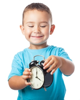 Smiling child playing with an alarm clock