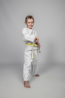 Улыбающийся ребенок, практикующий боевые искусства с деревянным боккеном.