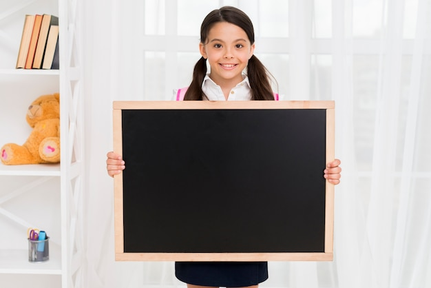 Smiling child in school uniform showing blackboard in classroom