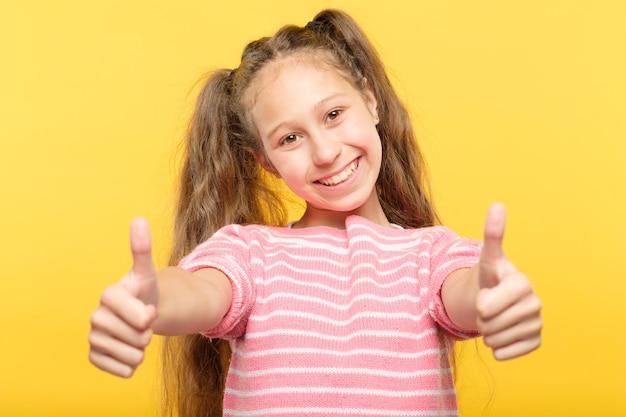 2つの親指を上げて笑顔の子供。成功と承認の概念。