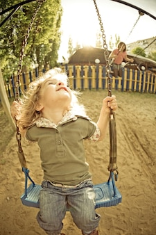 Smiling child on swing on playground vintage look shot was taken with fisheye lens