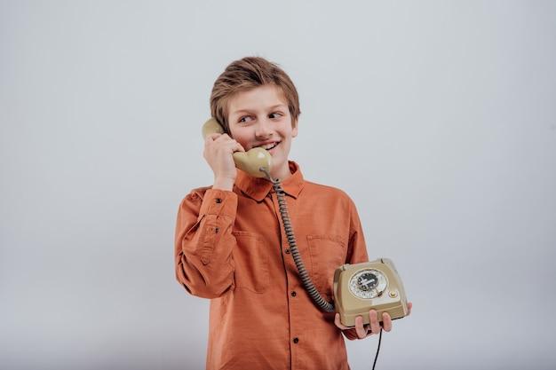 흰색 배경에 고립 된 오래 된 전화에 얘기 웃는 아이