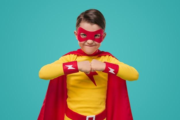 スーパーヒーローのマントとマスクを身に着けている笑顔の子供がスタジオで青い背景に拳をぶつけてカメラを見て