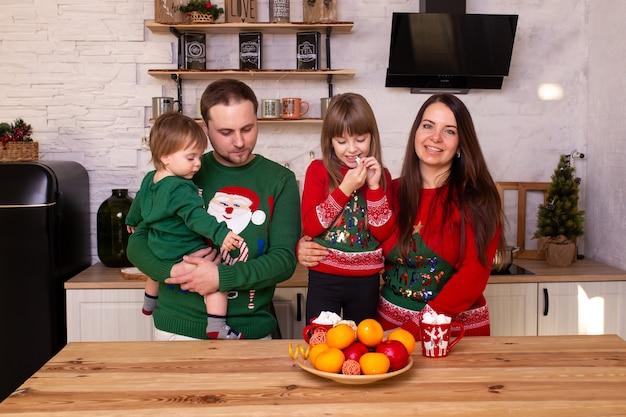 家でクリスマスを待っている笑顔の子供たちとその両親