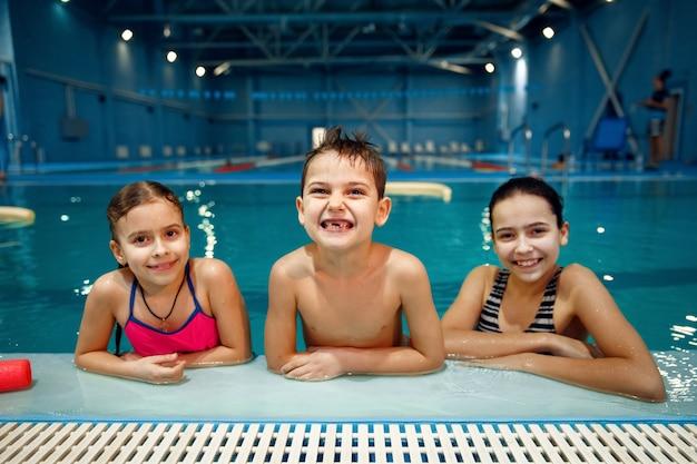 Улыбающиеся дети группы позы у бассейна, тренировки по плаванию