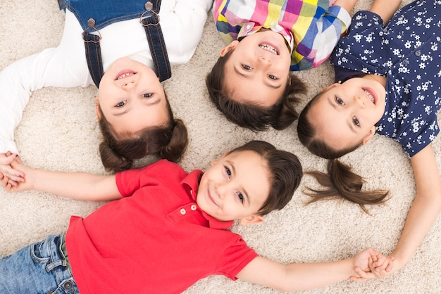 Smiling children lying down