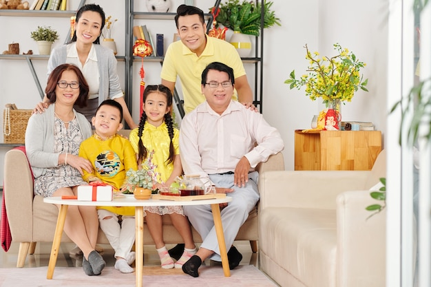 Smiling children, parents and grandparents gathered at home to celebrate lunar new year, decorations with best wishes in background