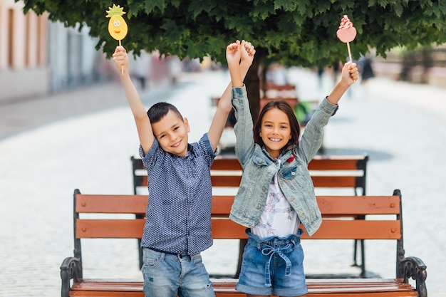 Smiling children with lollipops, near the wooden bench in the park