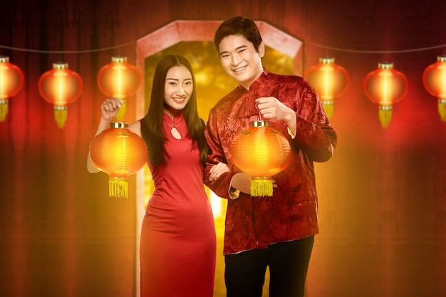 Smiling chinese couple with cheongsam dress holding red lanterns